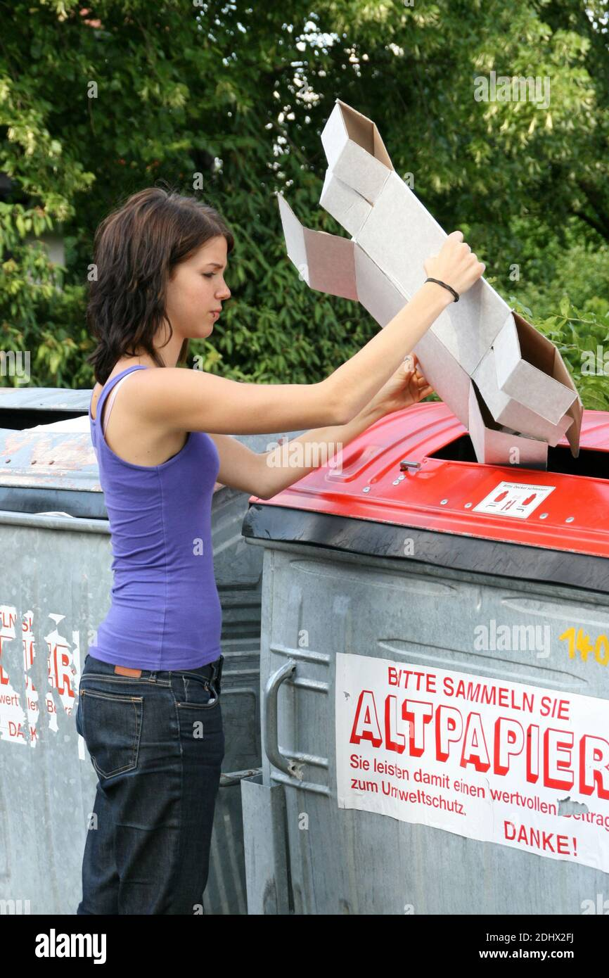 Frau entsorgt Altpapier im Container, MR: Yes Stock Photo