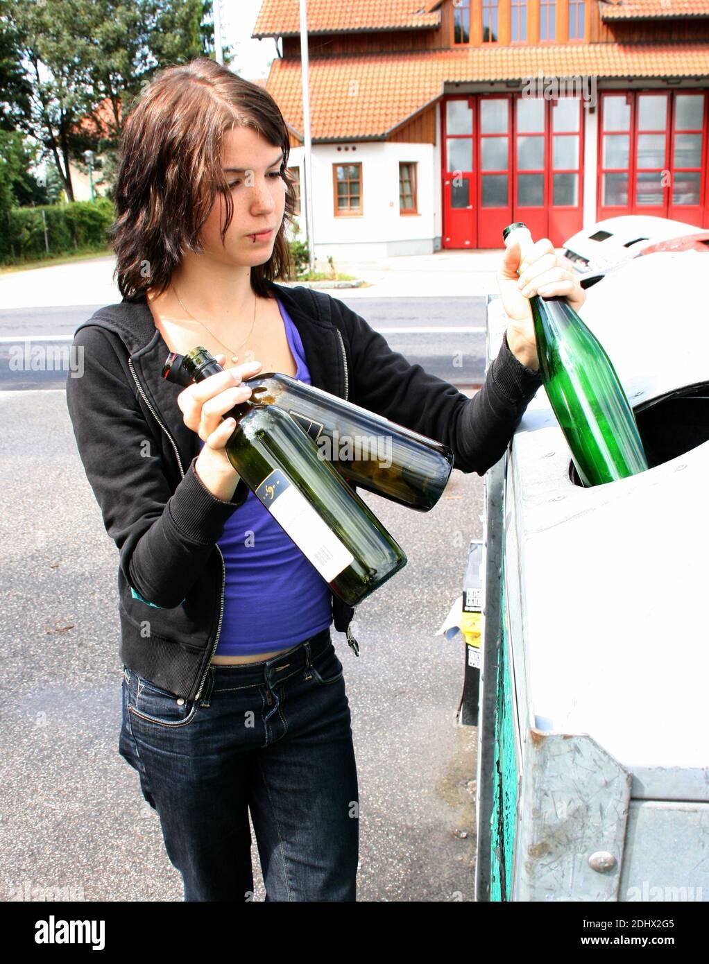 Frau entsorgt Altglas im Container, MR: Yes Stock Photo