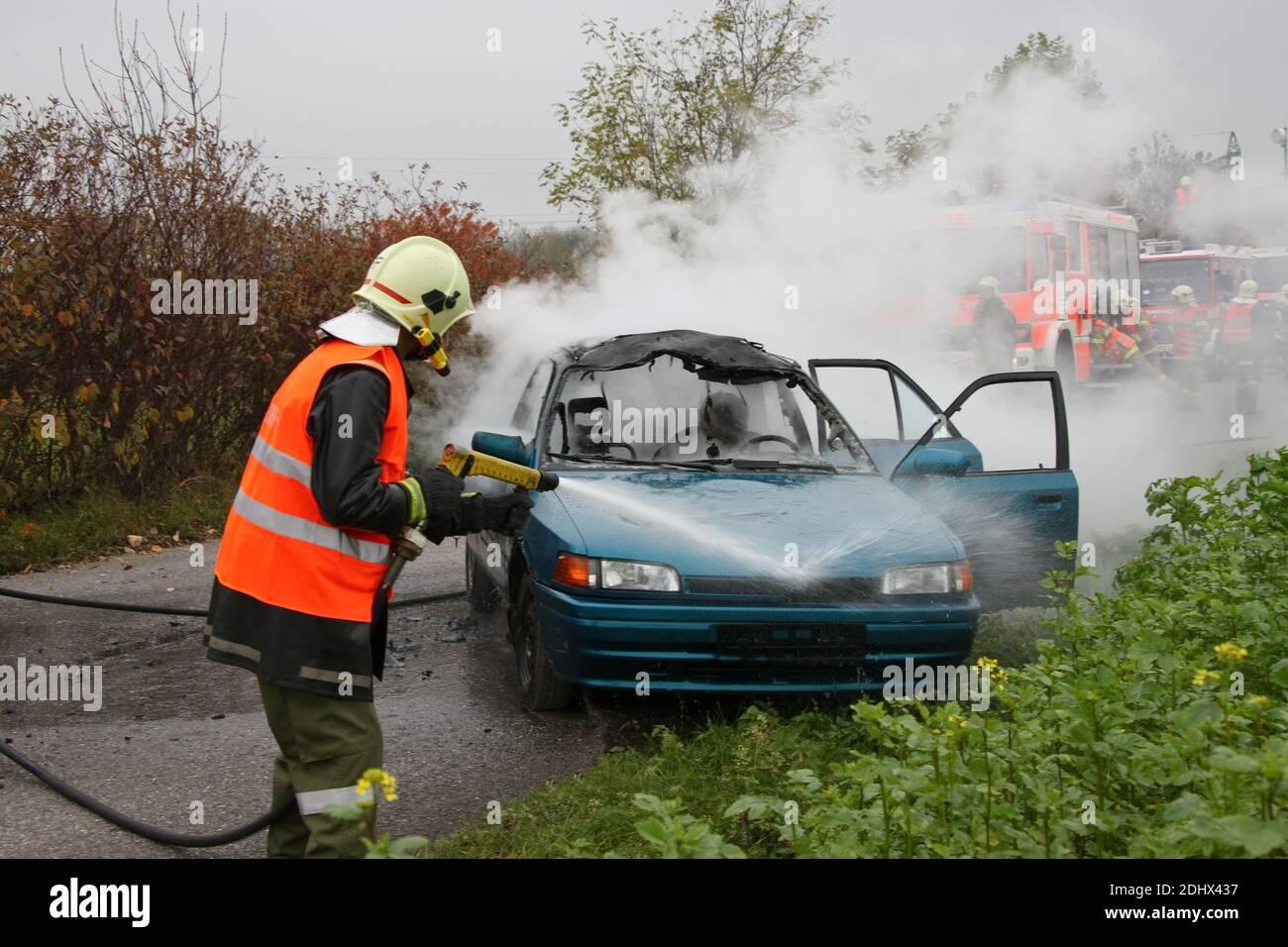 Feuerwehr loescht ein brennendes Auto, Verkehrsunfall, Stock Photo
