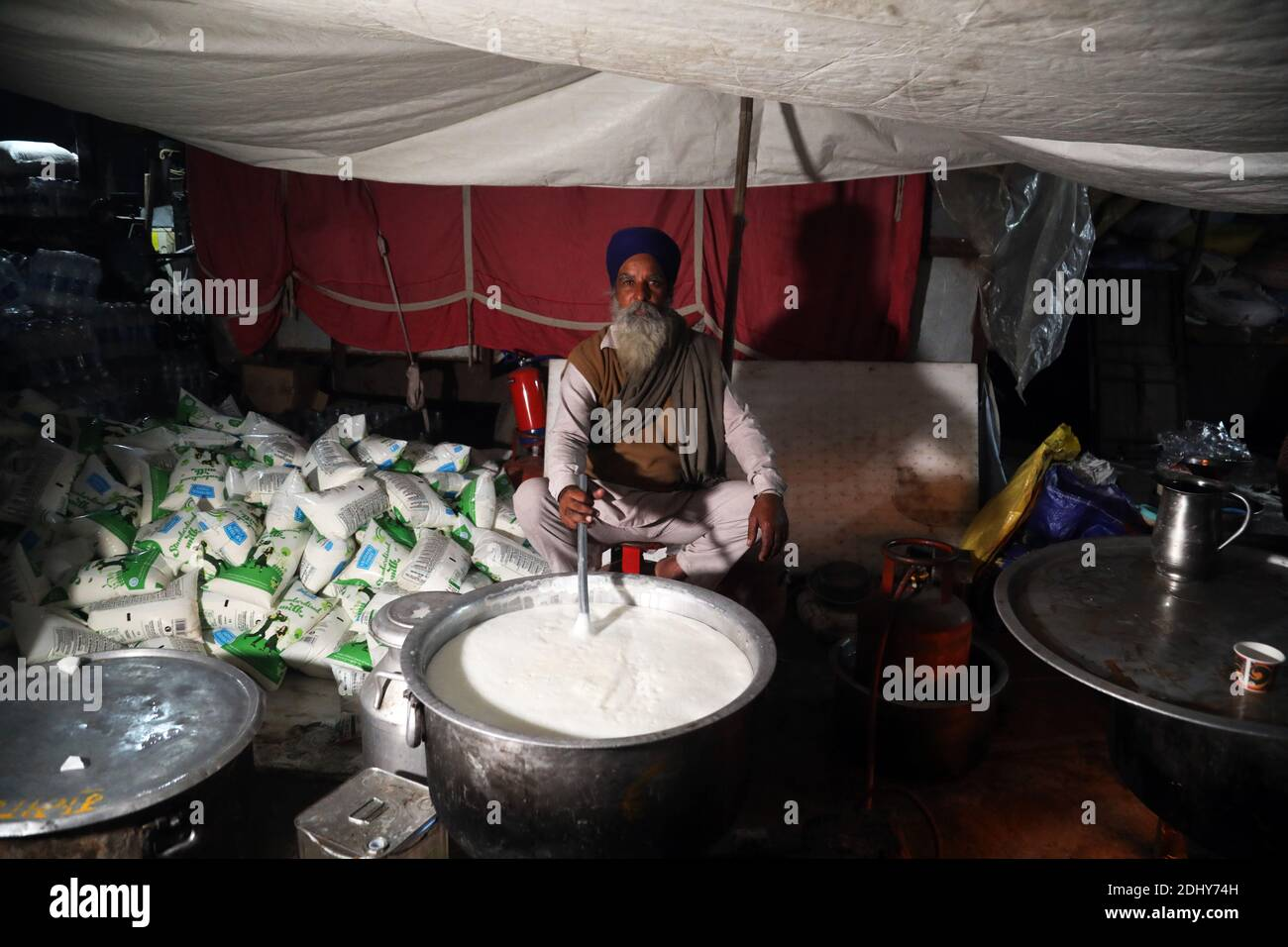 A protester preparing milk for colleagues in a community kitchen during the demonstration.Thousands of farmers from Punjab, Haryana and Uttar Pradesh blocked Singhu border (Delhi-Haryana Highway), Ghazipur border (Delhi-Meerut Highway), Tikri border and Gurugram Border agitating for the 17 days. Against the Centre's new farm reform laws.  Indian Union Minister of Agriculture and Farmers Welfare, Narendra Singh Tomar appeals to farmers to end their protest and work with the government. Stock Photo
