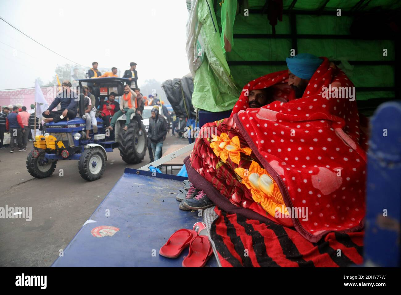 Protesters use a blanket to warm themselves during the demonstration.Thousands of farmers from Punjab, Haryana and Uttar Pradesh blocked Singhu border (Delhi-Haryana Highway), Ghazipur border (Delhi-Meerut Highway), Tikri border and Gurugram Border agitating for the 17 days. Against the Centre's new farm reform laws.  Indian Union Minister of Agriculture and Farmers Welfare, Narendra Singh Tomar appeals to farmers to end their protest and work with the government. Stock Photo