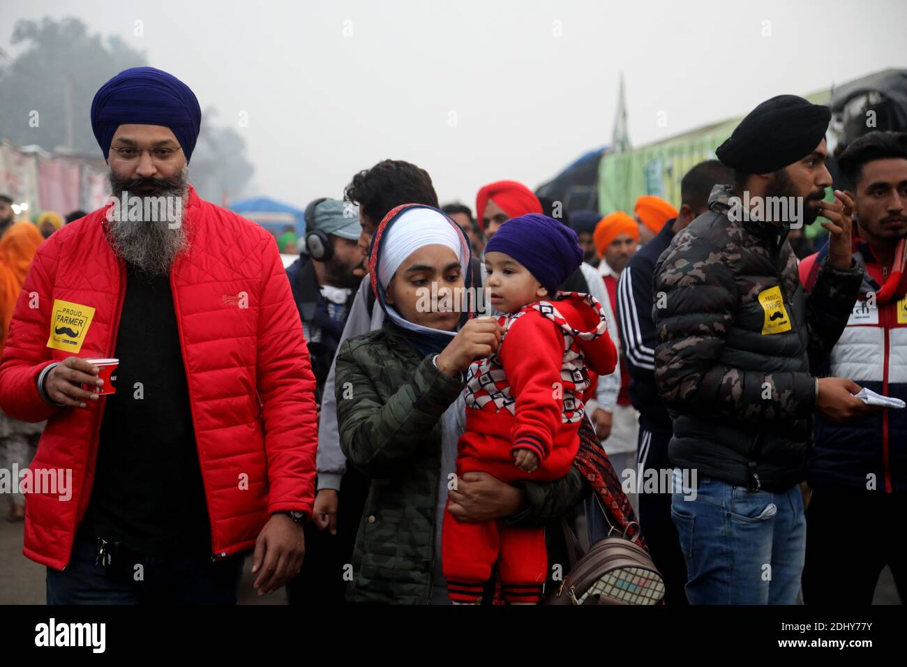 A protester carrying a baby during the demonstration.Thousands of farmers from Punjab, Haryana and Uttar Pradesh blocked Singhu border (Delhi-Haryana Highway), Ghazipur border (Delhi-Meerut Highway), Tikri border and Gurugram Border agitating for the 17 days. Against the Centre's new farm reform laws.  Indian Union Minister of Agriculture and Farmers Welfare, Narendra Singh Tomar appeals to farmers to end their protest and work with the government. Stock Photo