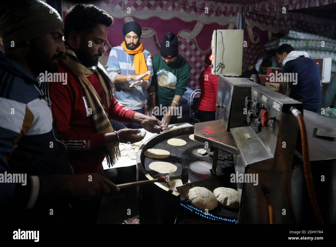 Protesters preparing meals for colleagues in a community kitchen conducted by Sikh organization during the demonstration. Thousands of farmers from Punjab, Haryana and Uttar Pradesh blocked Singhu border (Delhi-Haryana Highway), Ghazipur border (Delhi-Meerut Highway), Tikri border and Gurugram Border agitating for the 17 days. Against the Centre's new farm reform laws.  Indian Union Minister of Agriculture and Farmers Welfare, Narendra Singh Tomar appeals to farmers to end their protest and work with the government. Stock Photo