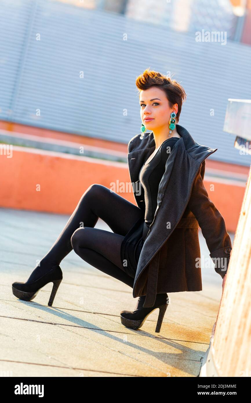 Teengirl kneeling kneel on street legs heels eyeshot eyes eye contact looking at camera Blue earring earrings ear ring rings Stock Photo
