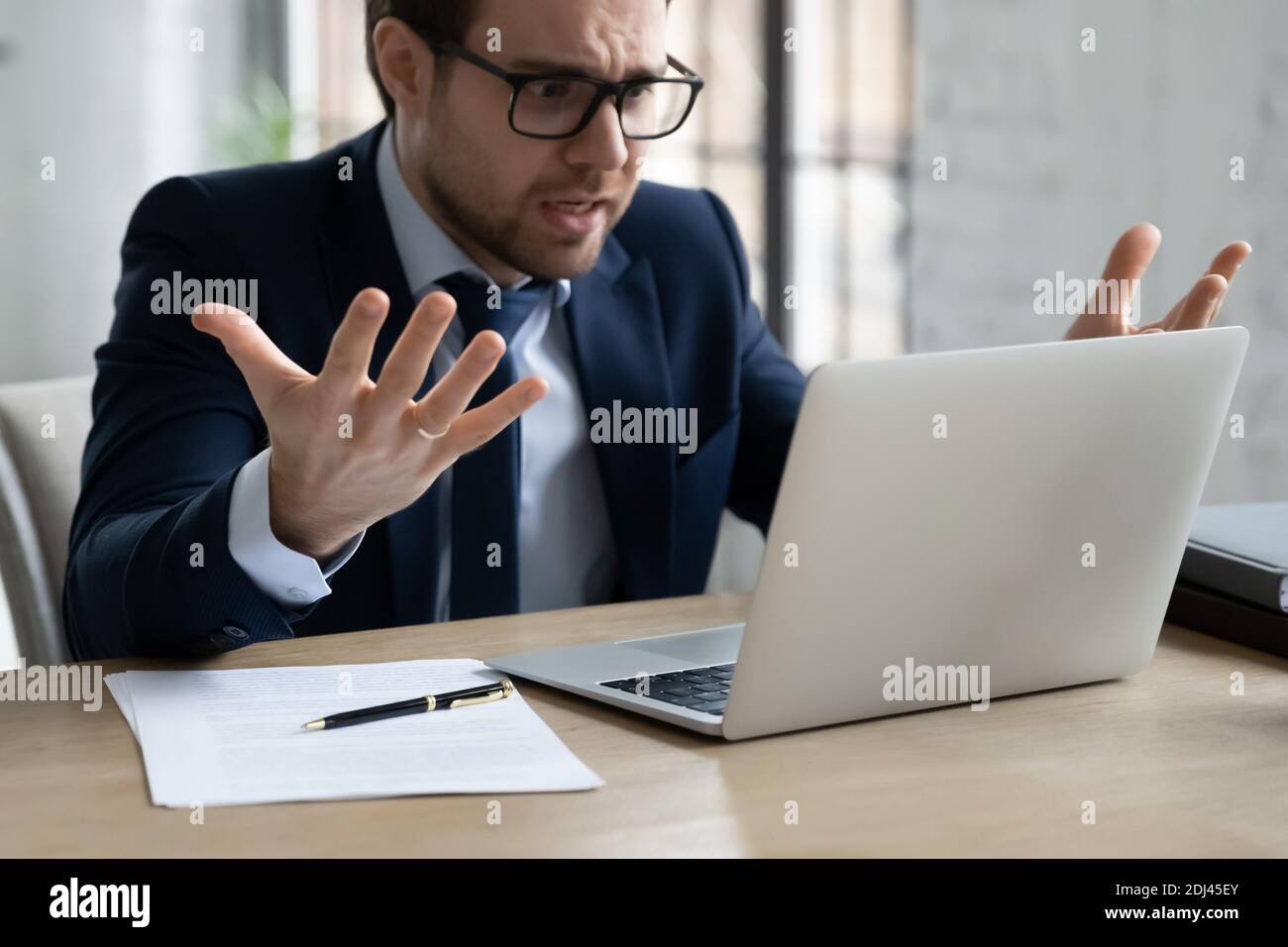 Close up annoyed businessman wearing glasses looking at laptop screen Stock Photo
