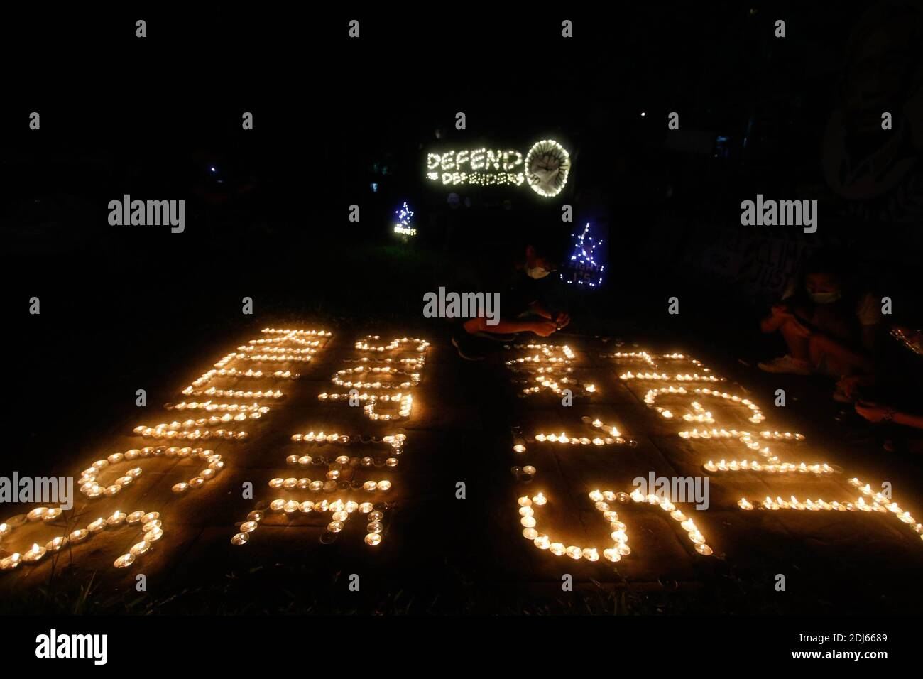 Climate activists lit candles and held LED lighting banners on December 11th 2020. This activity commemorates the five year anniversary of the Paris Agreement with a call to fight for 1.5 and to end the killing of environmental defenders. Quezon City, Philippines. Stock Photo