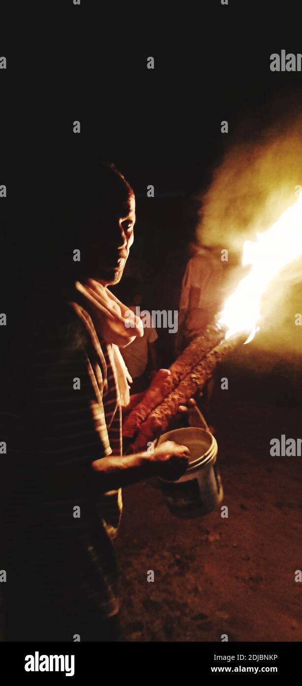 Side View Of Mature Man Holding Fire While Standing Against Sky At Night Stock Photo