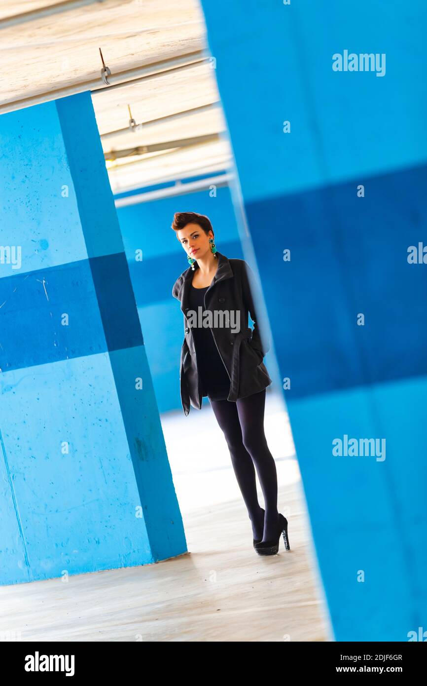 Teengirl in empty parking lot with Blue walls legs heels eyeshot eyes eye contact looking at camera tight space serious unsmiling Stock Photo