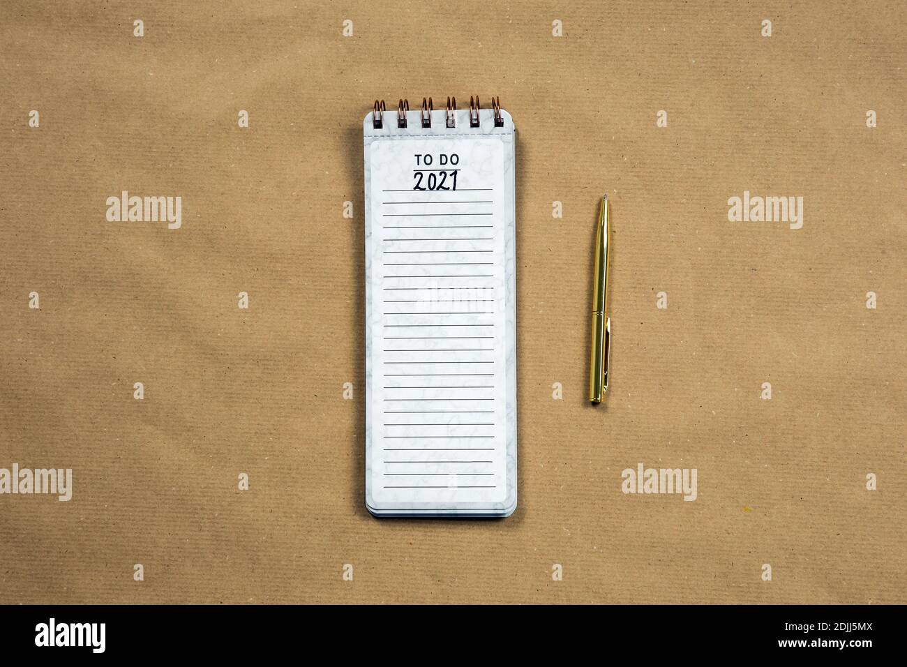 Planning New Year goald on empty notepad in the year 2021, top view on brown background texture, top view copy space, space for text modern design Stock Photo