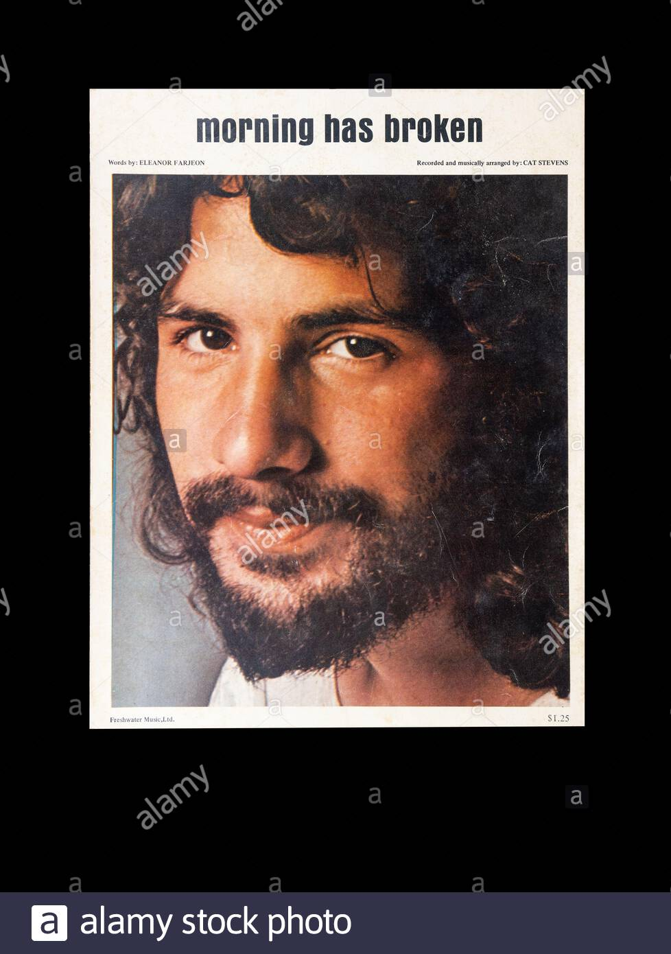 "SHEET MUSIC IMAGE isolated on black background.  The music for ""Morning has Broken"", by Cat Stevens.  Shows portrait of Stevens. Stock Photo"