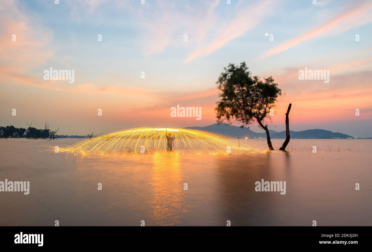 Showers of hot glowing sparks from spinning steel wool near the alone tree Stock Photo