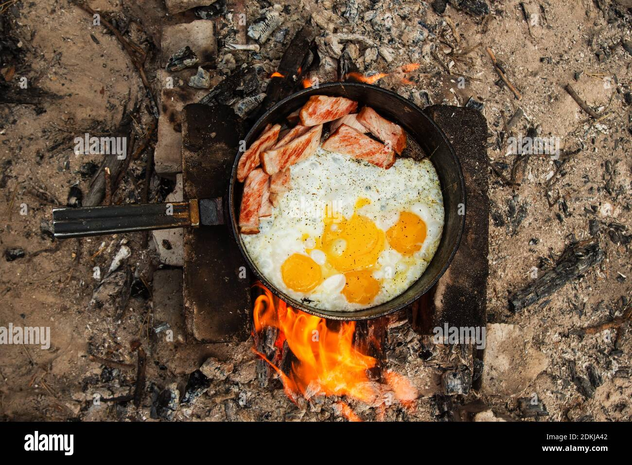 Scrambled eggs with bacon on the cast-iron pan on a bonfire, top view. Stock Photo