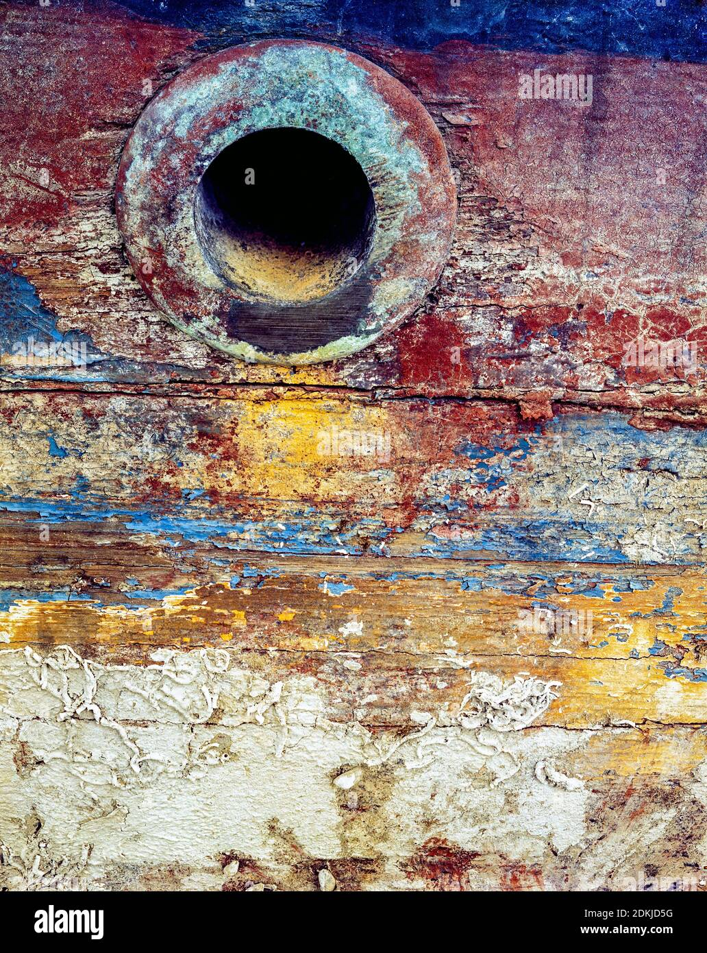 UK, London, Docklands, Isle of Dogs, shipping docks, early 1974. The worn hull of an old boat showing many layers of paint and sea worms calcium deposits by the coolant water outlet. Stock Photo