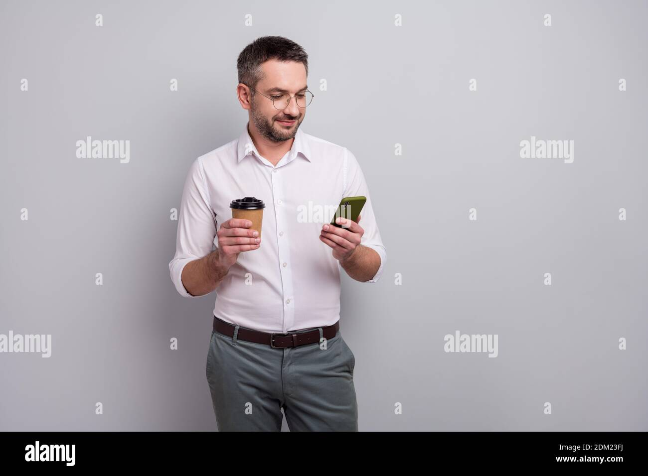 Portrait of his he nice attractive cheery elegant classy mature man holding in hands cell chatting online drinking cacao isolated over light gray Stock Photo