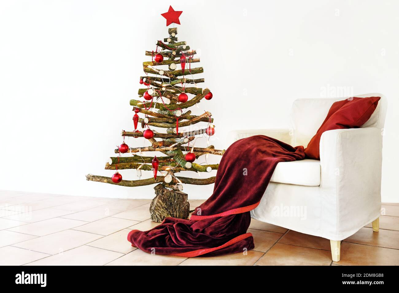 Homemade Alternative Christmas Tree Of Rustic Raw Wood Branches Decorated With Fairy Lights And Red Balls Next To An Armchair With Wool Blanket Copy Stock Photo Alamy