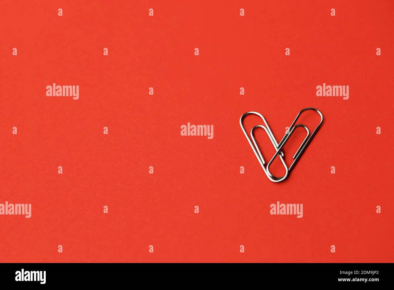 Heart shape paper clips on a red background. Valentine's day concept. High quality photo Stock Photo