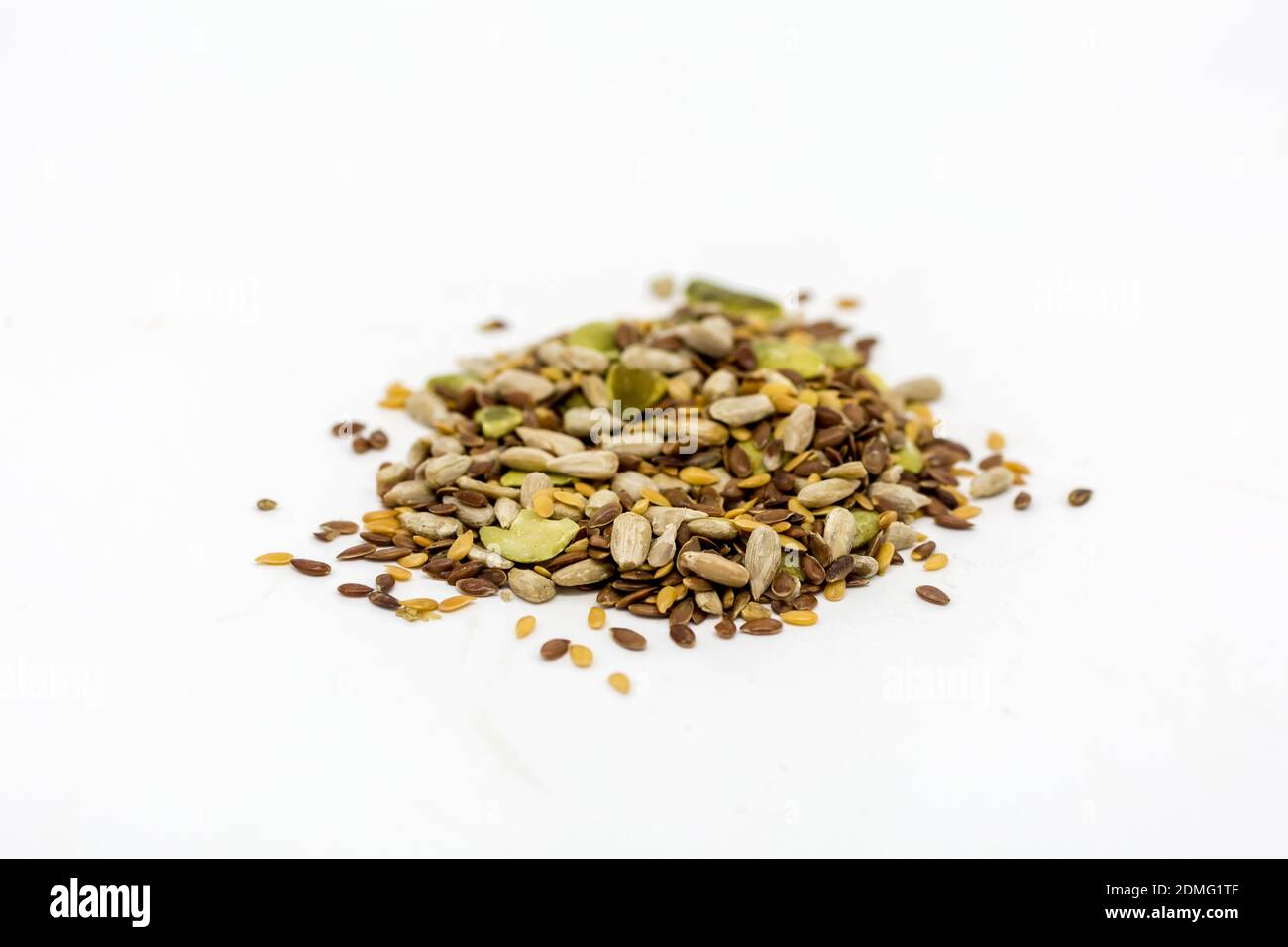 A pile of mixed seeds against a white background Stock Photo