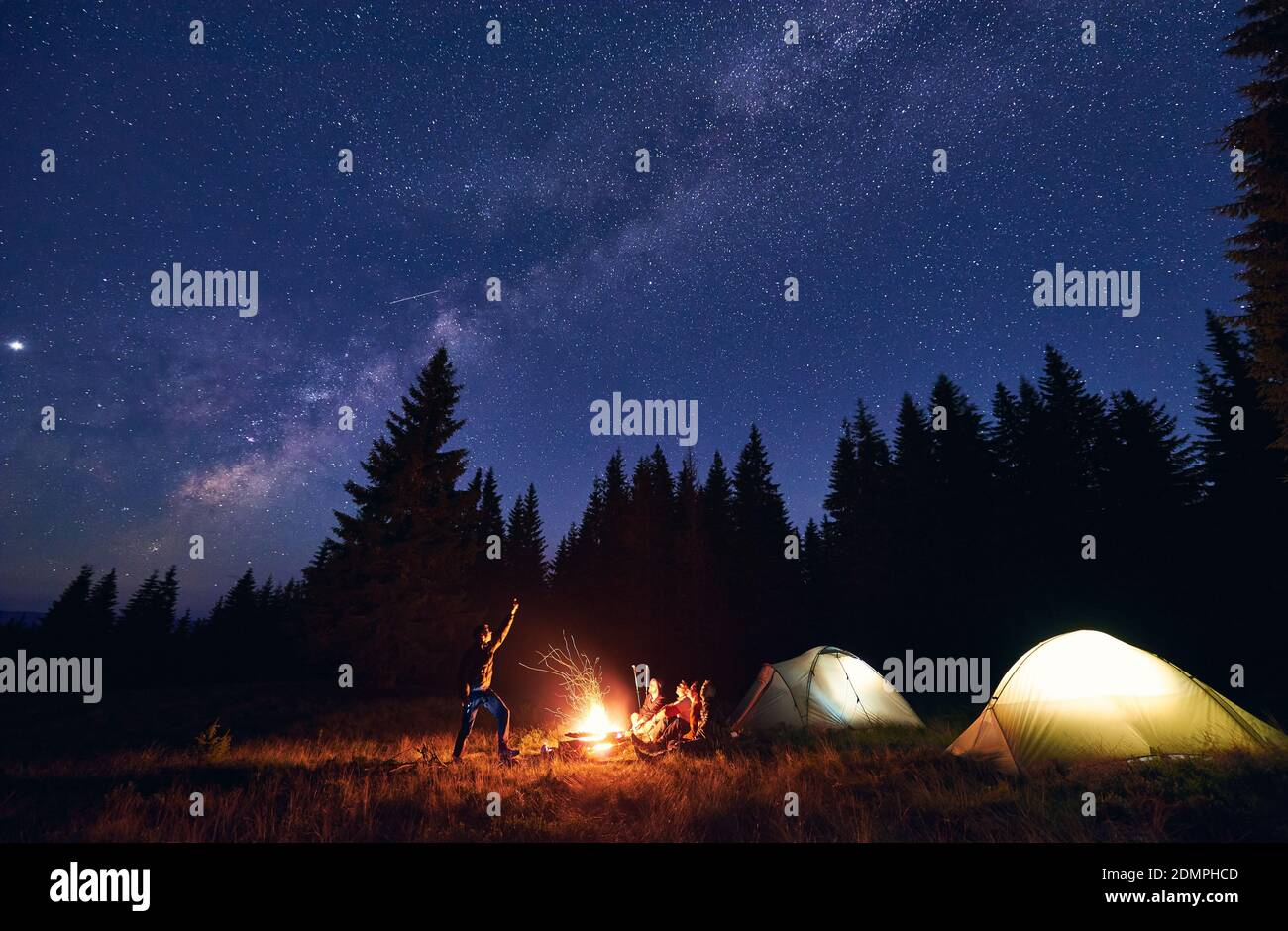 Man showing his friends Milky Way over tent city. Guys are sitting by the campfire on the background of the spruce forest and enjoying the evening starry sky. Outdoor recreation, touristm concept Stock Photo