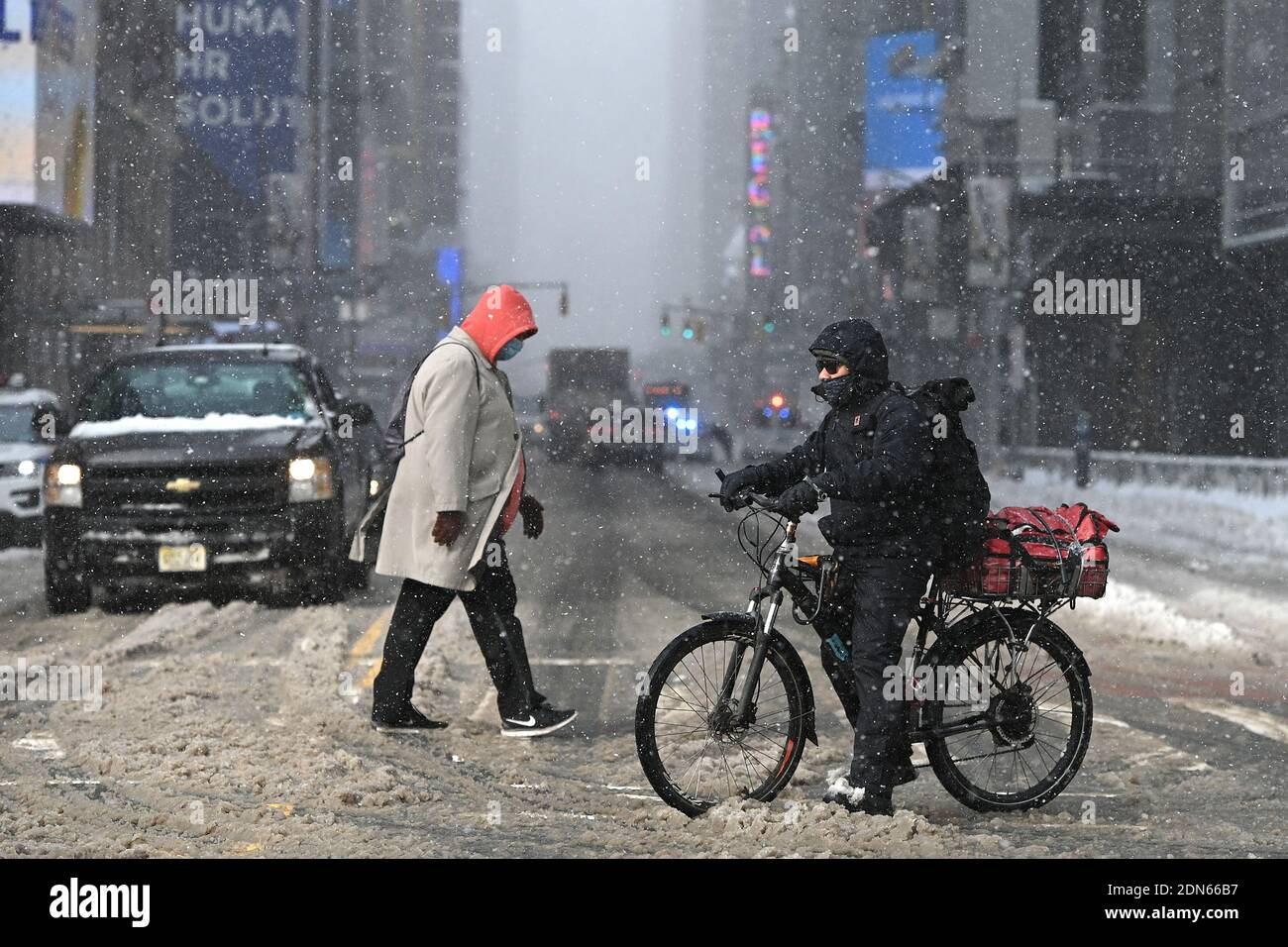 New York, USA. 17th Dec, 2020. A food delivery person on a bicycle waits to cross 42nd Street at the tail end of a nor'easter that brought more than a foot of snow to some parts of the city, New York, NY, December 17, 2020. As a COVID-19 pandemic second wave grips the United States, restaurants continue to struggle as cities like New York have one again banned indoor dining, as well as outdoor dining during the snowstorm. (Photo by Anthony Behar/Sipa USA) Credit: Sipa USA/Alamy Live News Stock Photo