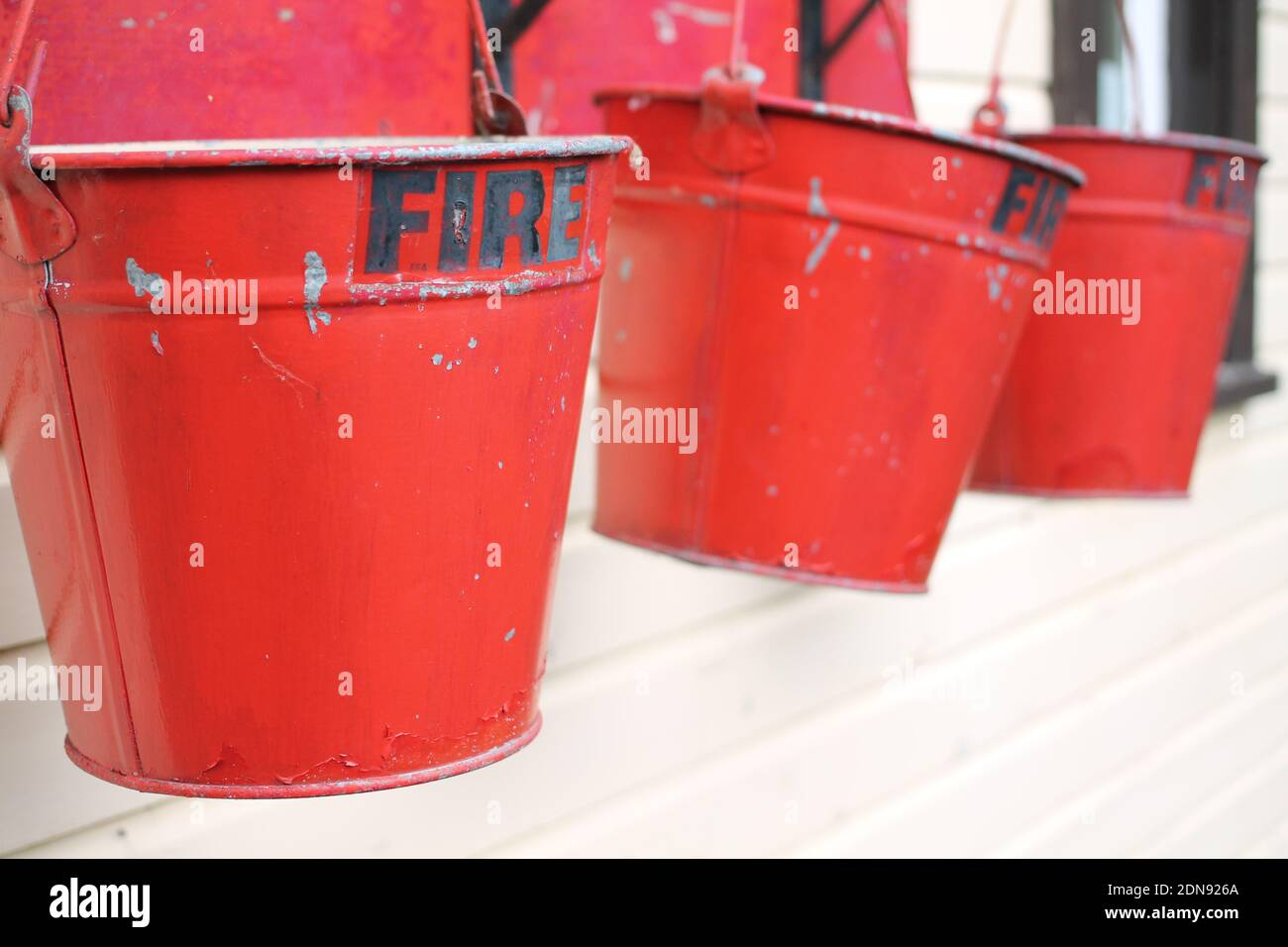 Close-up Of Red Metal Buckets With Fire Text Hanging Against Wall Stock Photo
