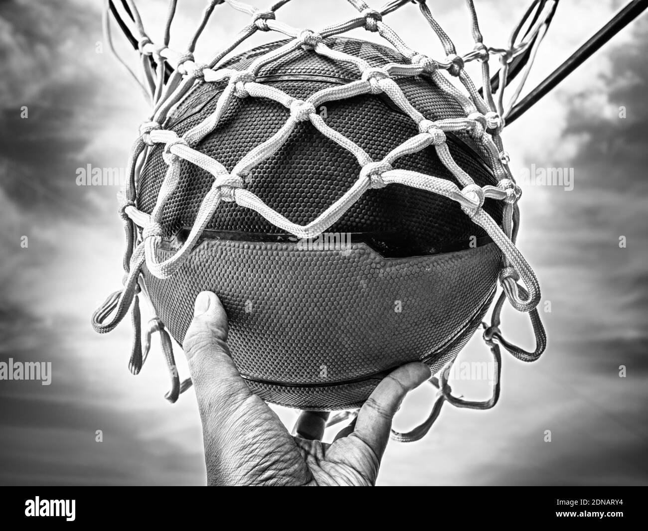 Cropped Hand Holding Ball In Basketball Hoop Stock Photo