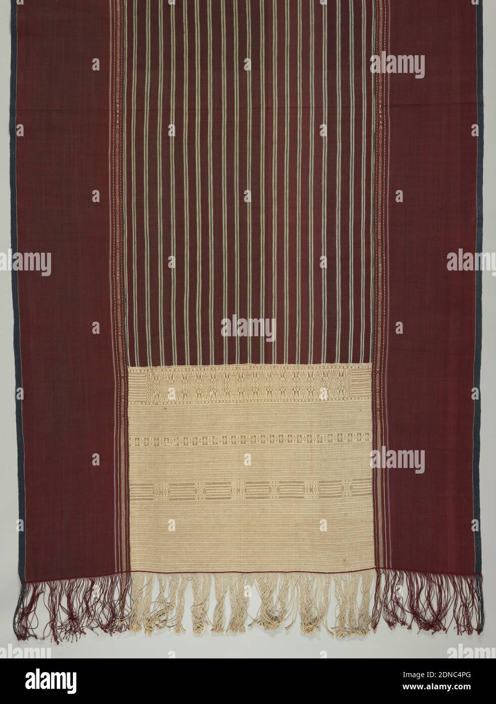 Ulos ragidup (ceremonial shoulder cloth), Medium: cotton Technique: tied resist patterning in warp or weft (ikat) on plain weave, with supplementary weft patterning, Ulos ragidup, 'the cloth with the pattern of life', is a large ceremonial selendang (shoulder cloth) which is wrapped around the groom's mother by the bride's father at a wedding. Center area in dark maroon with vertical stripes of light blue and a bright red-brown. Ornamented on either end with intricate insets of cream color with horizontal bands of design, by making use of one additional warp. Wide borders in dark red Stock Photo