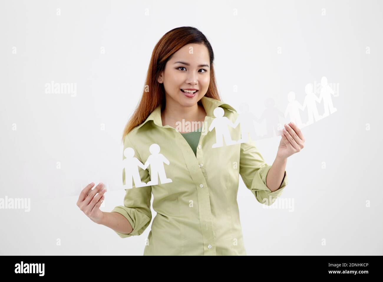 Portrait Of Happy Young Woman Holding People Paper Chains Against White Background Stock Photo
