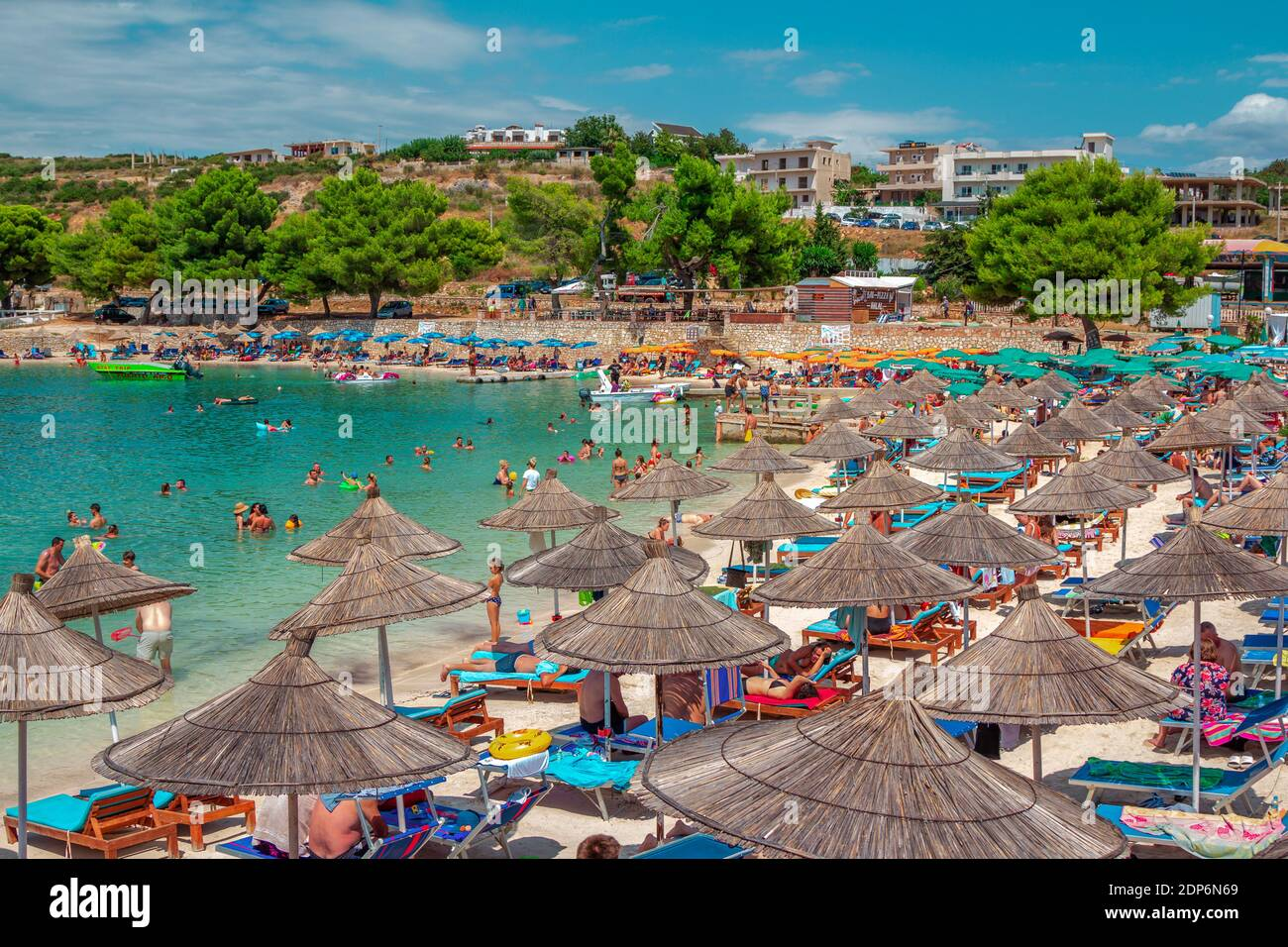 Ksamil, Albania - August 5, 2020: view of beautiful summer resort - sea bay with turquoise water, white sand, people, relaxing, tanning and swimming Stock Photo