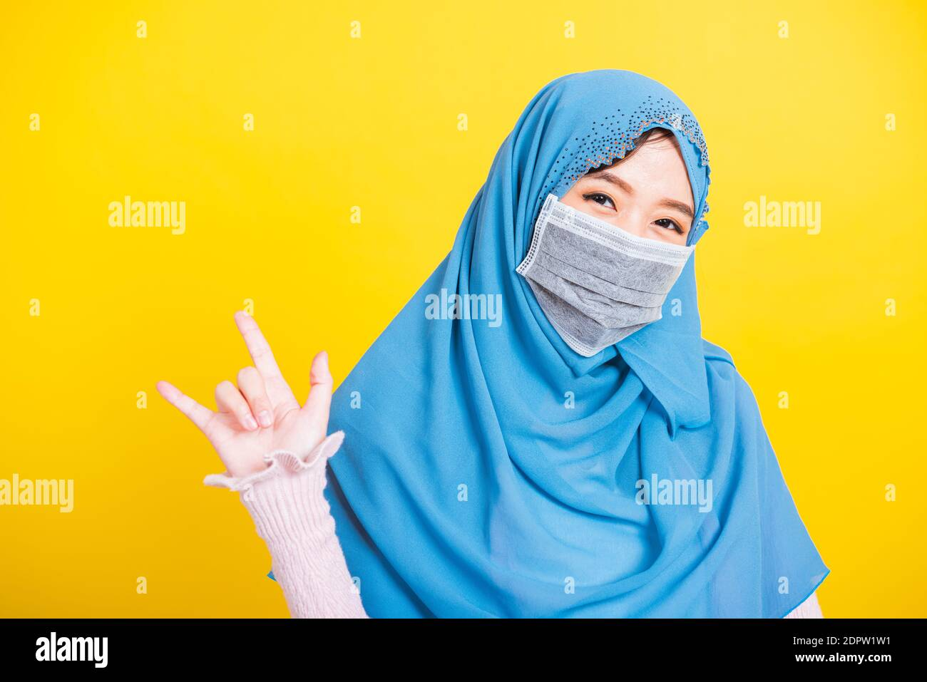 "Asian Muslim Arab, Portrait of happy beautiful young woman Islam religious wear veil hijab and face mask protect quarantines disease coronavirus show hand finger ""I LOVE YOU"" sign isolated yellow Stock Photo"