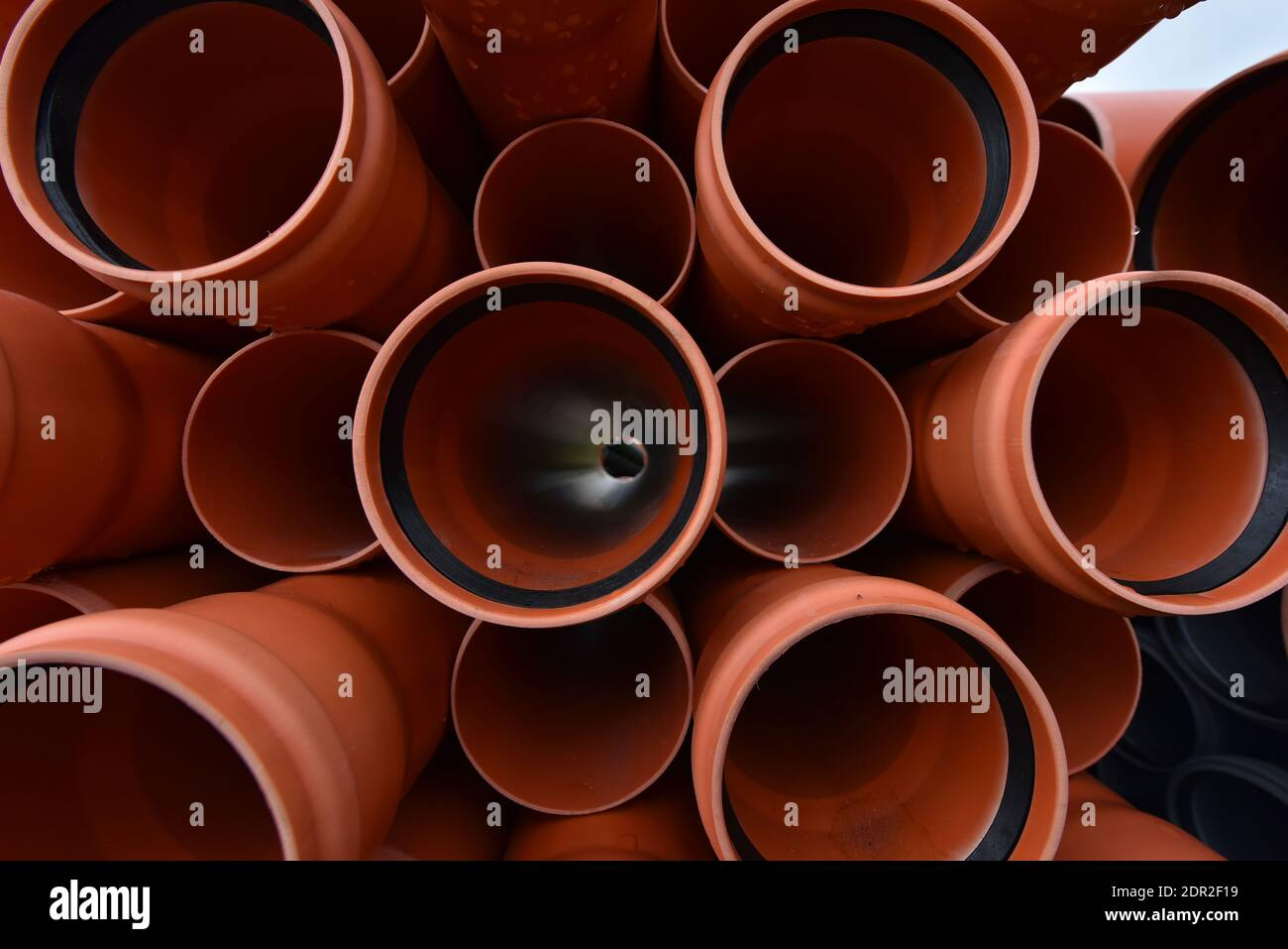 Large orange plastic pipes for sewerage system. Stock Photo
