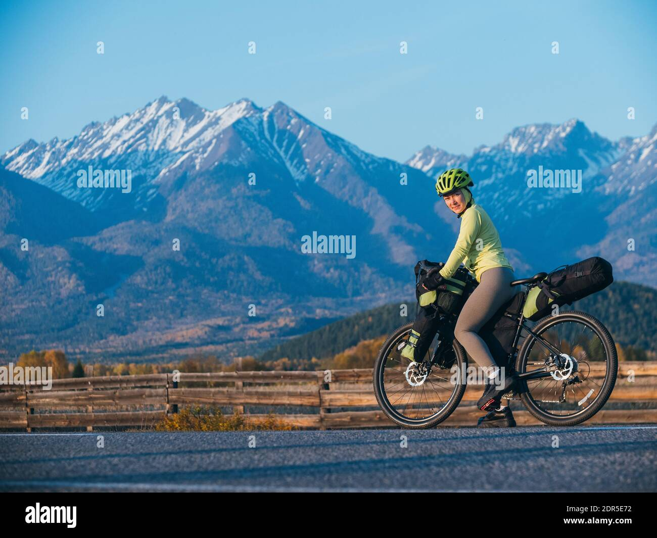 The woman travel on mixed terrain cycle touring with bikepacking. The traveler journey with bicycle bags. Sport tourism bikepacking. Stock Photo