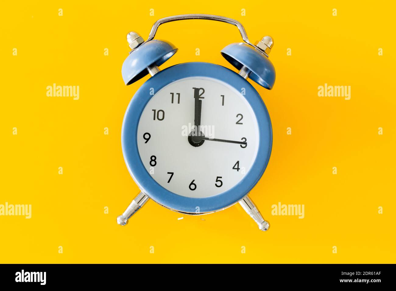 Stylish alarm clock showing five to twelve on a yellow background Stock Photo