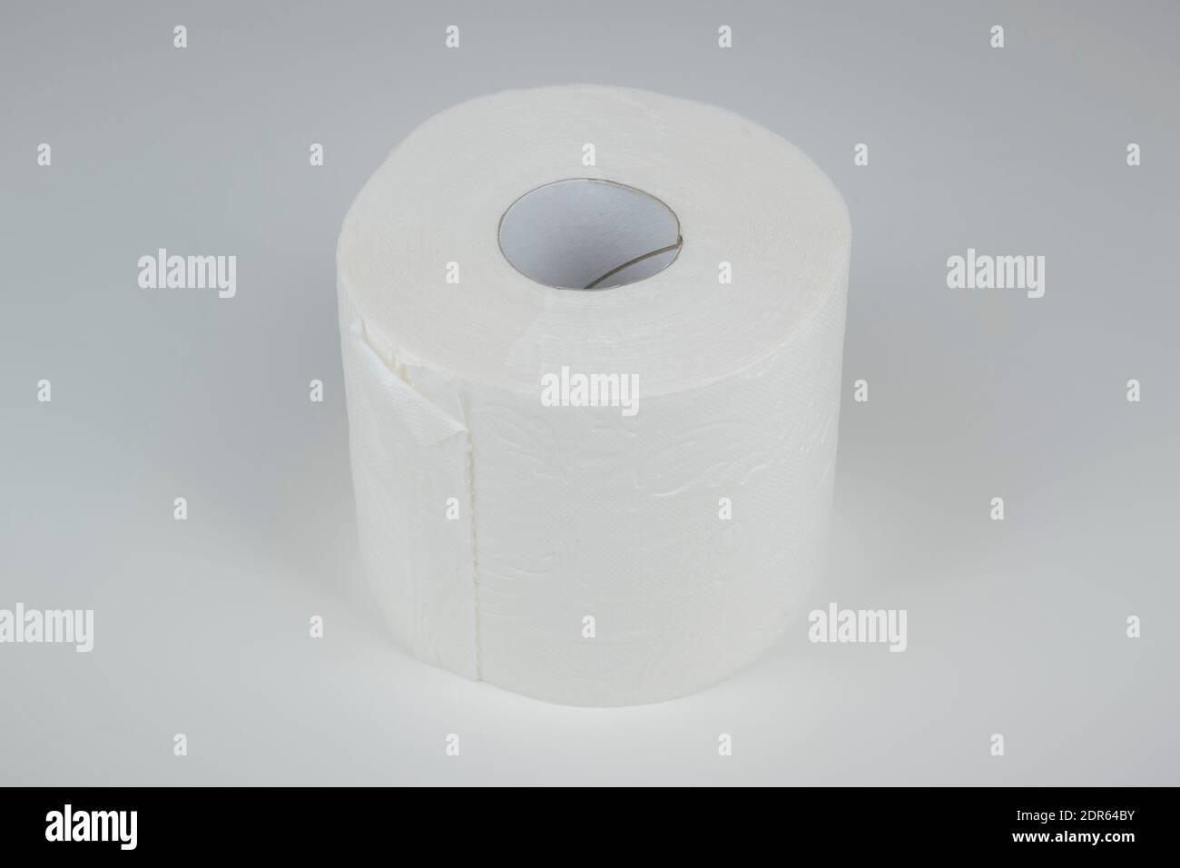 Eine Rolle Toilettenpapier auf weißem, neutralem Hintergrund. Stock Photo