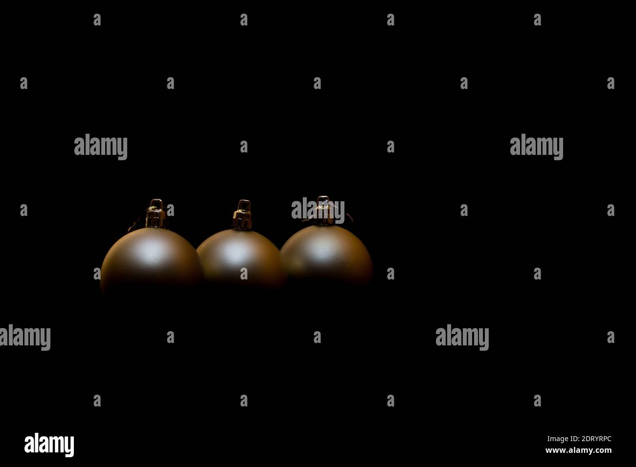Christmas decorations in the shape of a ball, golden color on a black background Stock Photo