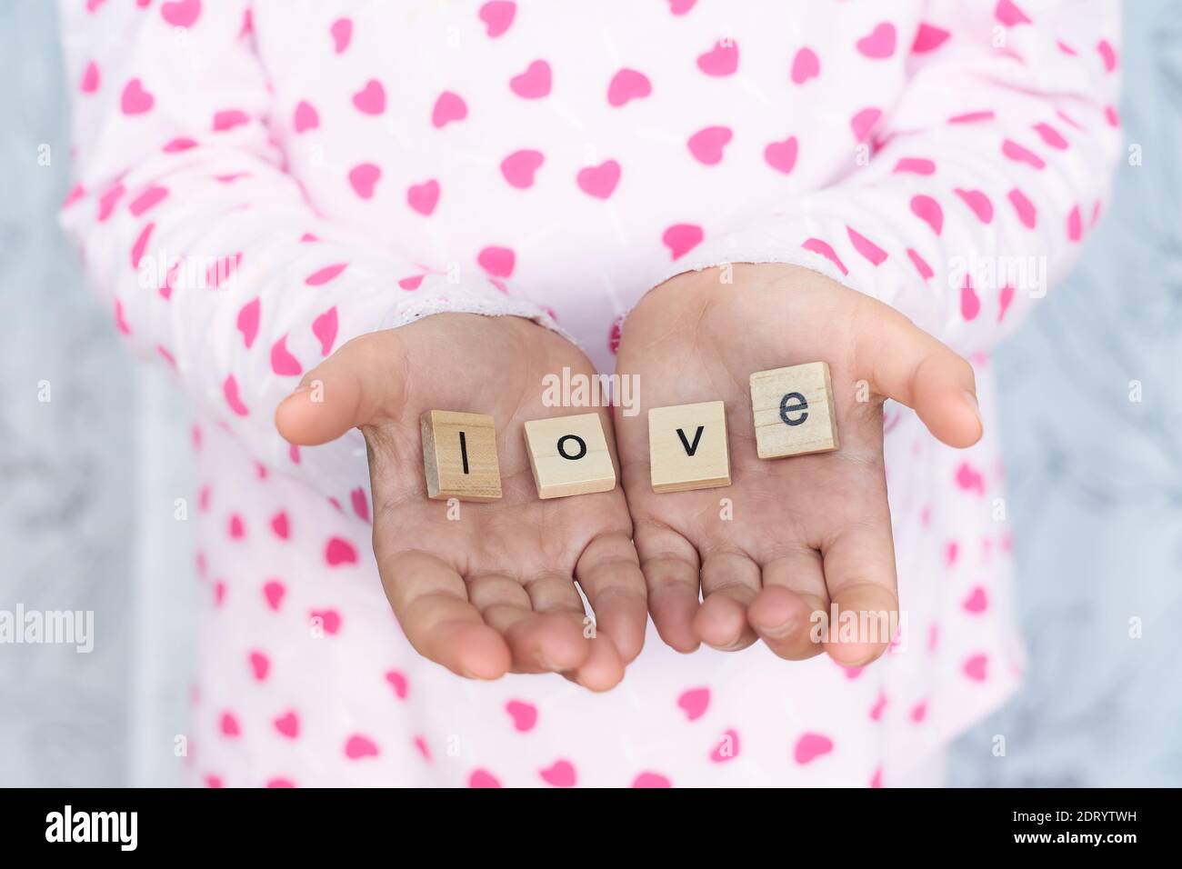 girl holds the word love in her hands , selective focus Stock Photo