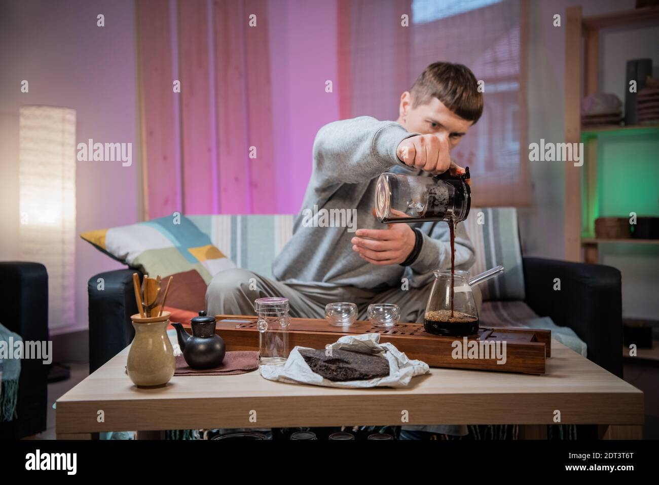 A young man is introduced to the Chinese culture of tea drinking. Brews fragrant raw tea at home. Pour boiling water over tea leaves Stock Photo