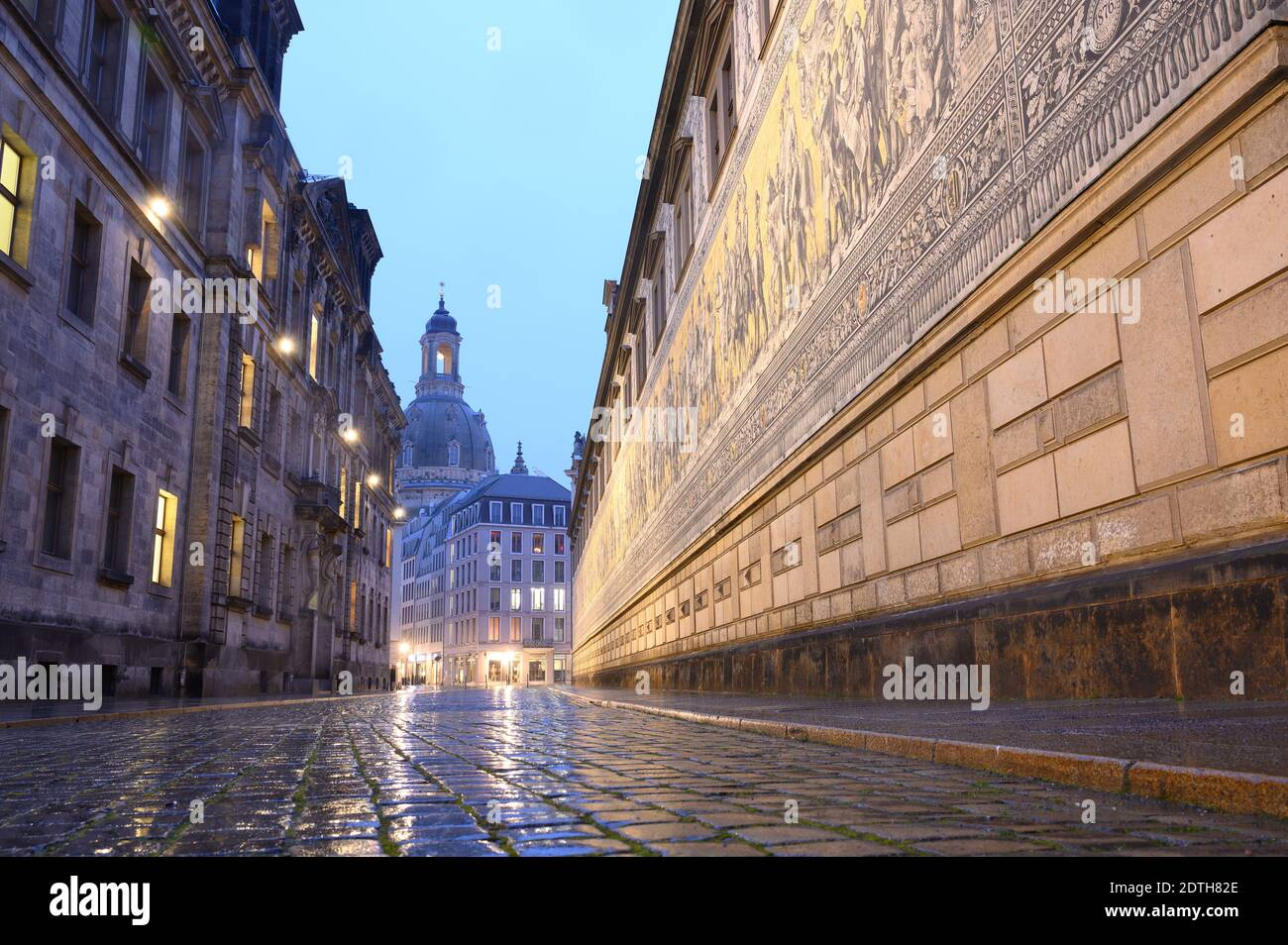 """Dresden, Germany. 22nd Dec, 2020. Augustusstrasse next to the mural """"Fürstenzug"""" (r) not far from the Frauenkirche (back) is deserted in the early morning. Germany is in a hard lockdown to contain the Corona pandemic. Credit: Sebastian Kahnert/dpa-Zentralbild/dpa/Alamy Live News Stock Photo"""