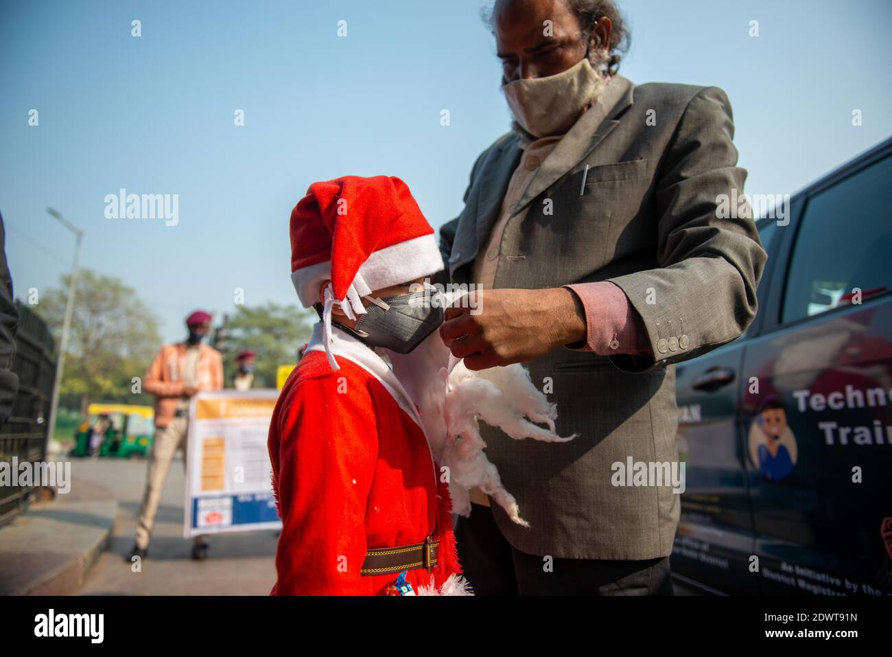 New Delhi, India. 23rd Dec, 2020. A man assisting a kid dressed up as Santa Claus to wear a face mask during the awareness campaign.The awareness campaign took place in Connaught Place, Delhi organized by the Office of District Magistrate to make people aware of Coronavirus pandemic precautionary measures. An artist and a boy attired like Santa Claus distributes masks among daily commuters. Credit: SOPA Images Limited/Alamy Live News Stock Photo