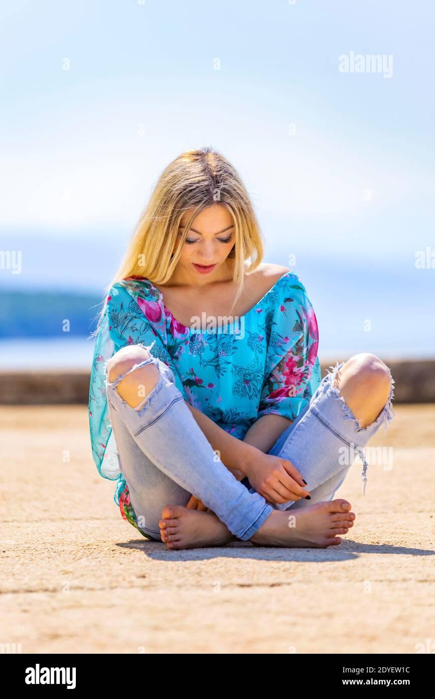 Blonde teengirl sitting on ground street crossed legs cross legged barefeet bare-feet wearing ripped denim denims pants barefoot Stock Photo