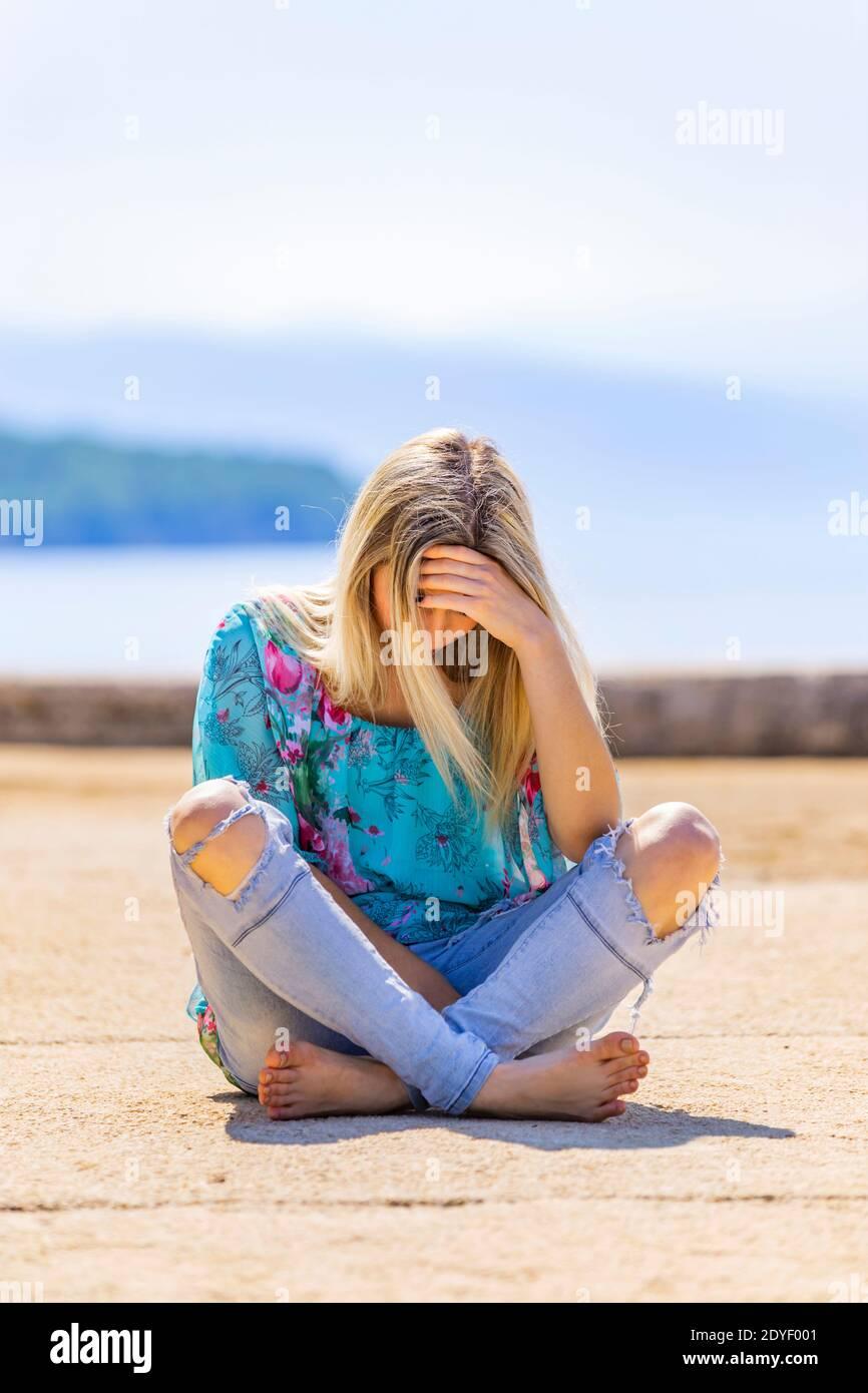 Blonde teengirl sitting on ground street crossed legs cross legged barefeet bare-feet wearing ripped denim denims pants Stock Photo
