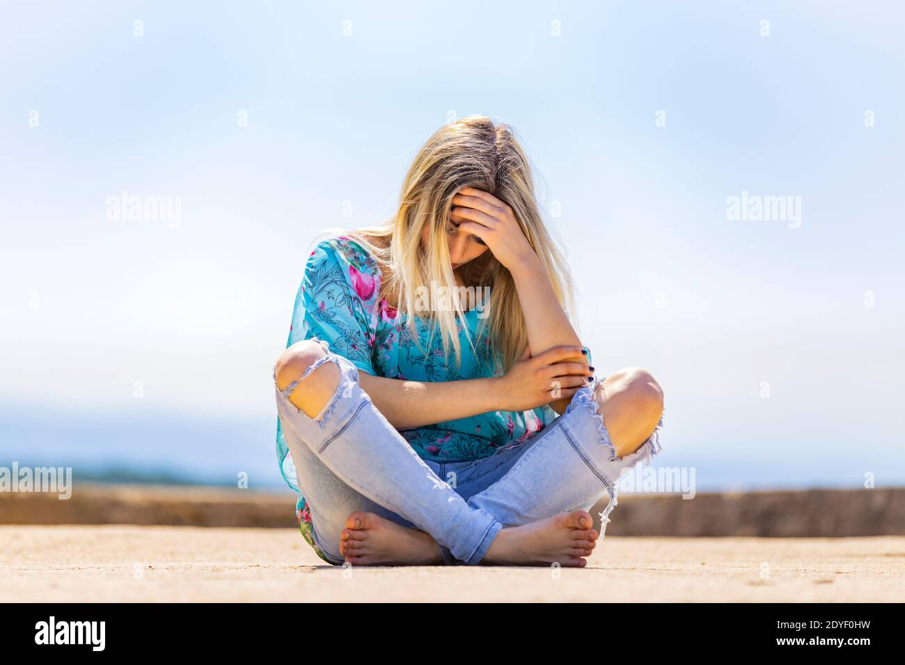 Blonde teengirl sitting on ground street crossed legs cross legged barefeet bare-feet wearing ripped denim denims pants low view Stock Photo