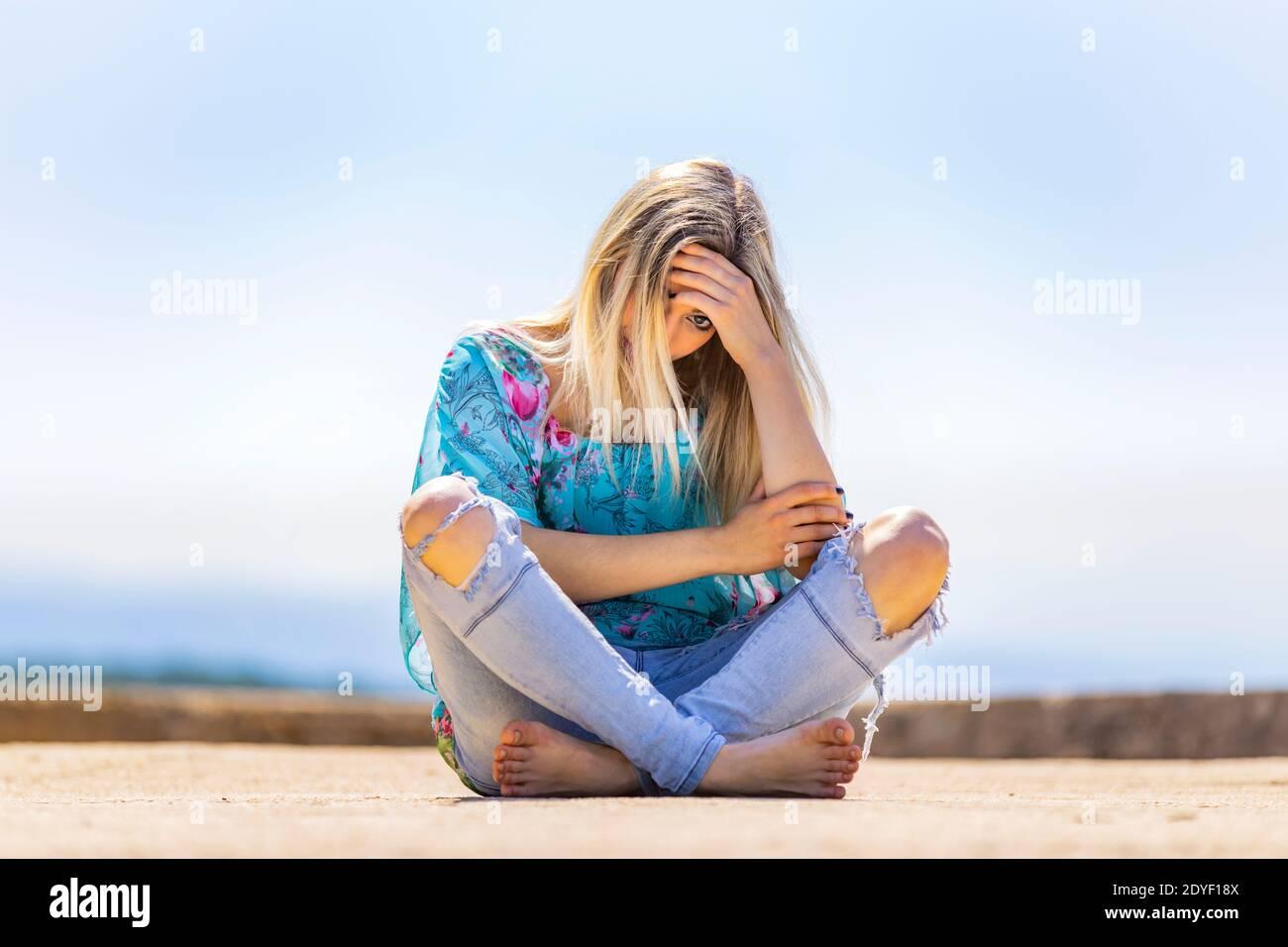 Blonde teengirl sitting on ground street crossed legs cross legged barefeet bare-feet wearing ripped denim denims pants low view peeking one eye shy Stock Photo