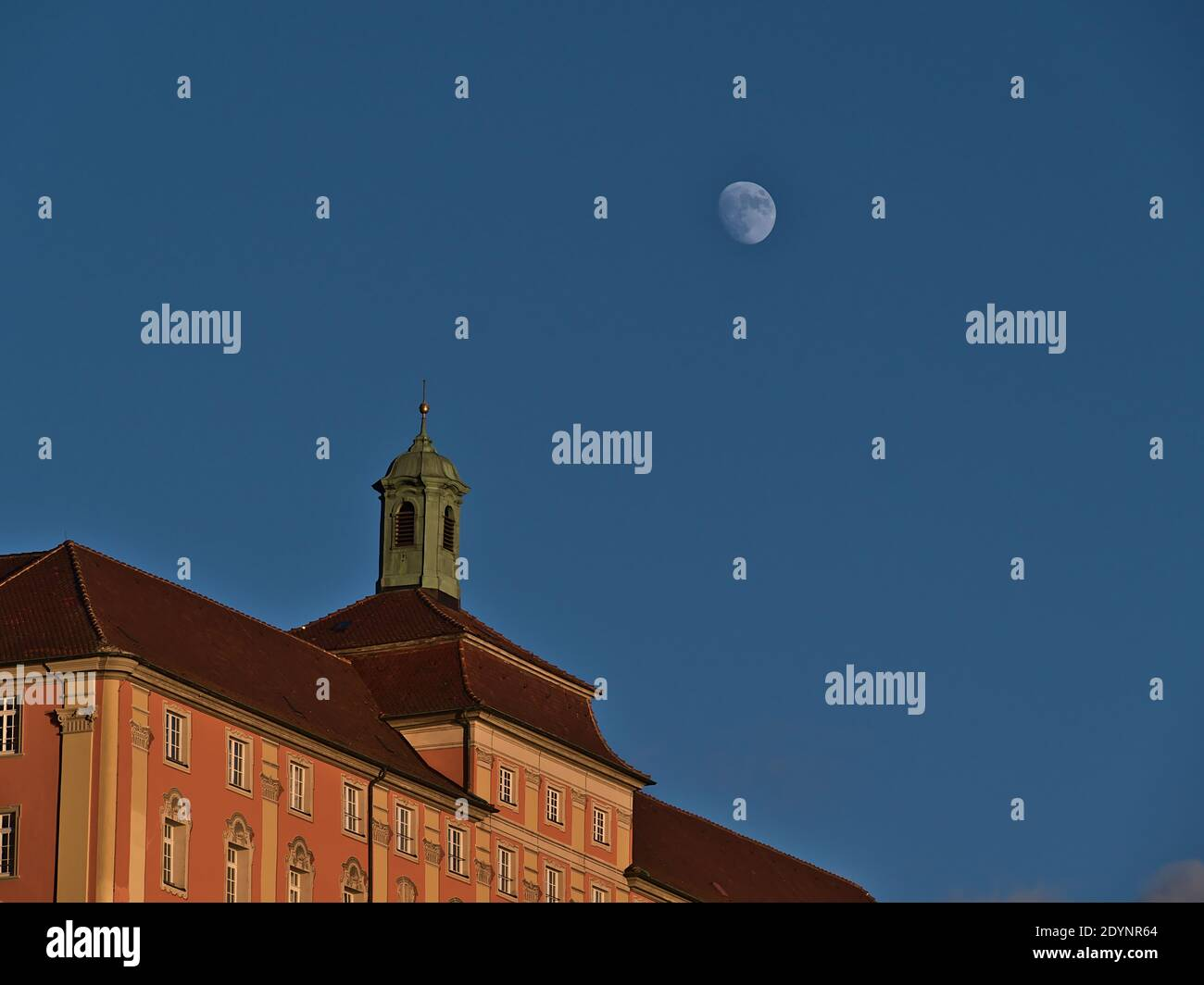 Historic building with pink colored decorated facade and small bell tower on the roof in beautiful evening light with moon visible in the blue sky. Stock Photo