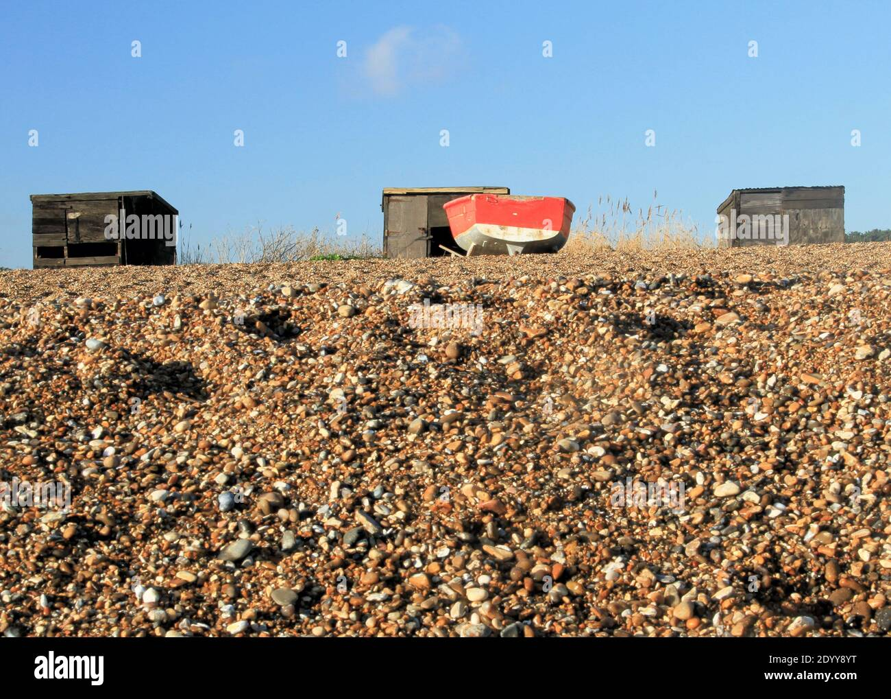 Fishing boat and huts on the beach at Dunwich, Suffolk Stock Photo