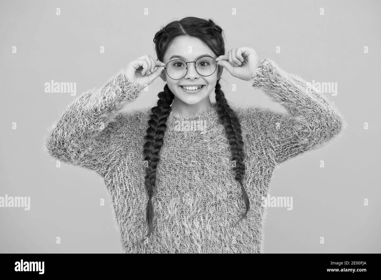 focus on what matters. cheerful teen has bad sight. Hair braided in braids. little beauty in glasses. happy childhood. small girl has nice smile. kid hairstyle fashion. smiling child with long hairdo. Stock Photo