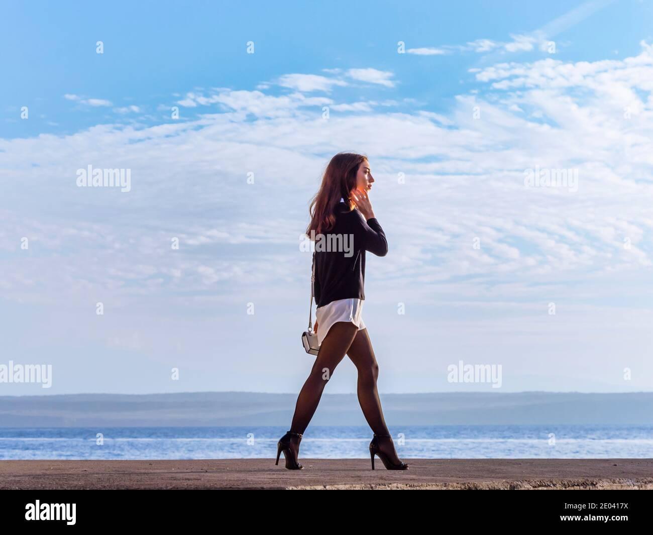 Teengirl walking fast on seaside promenade street near sea passing by pass walker walk sunny sunshine sunlight legs heels leggings Stock Photo