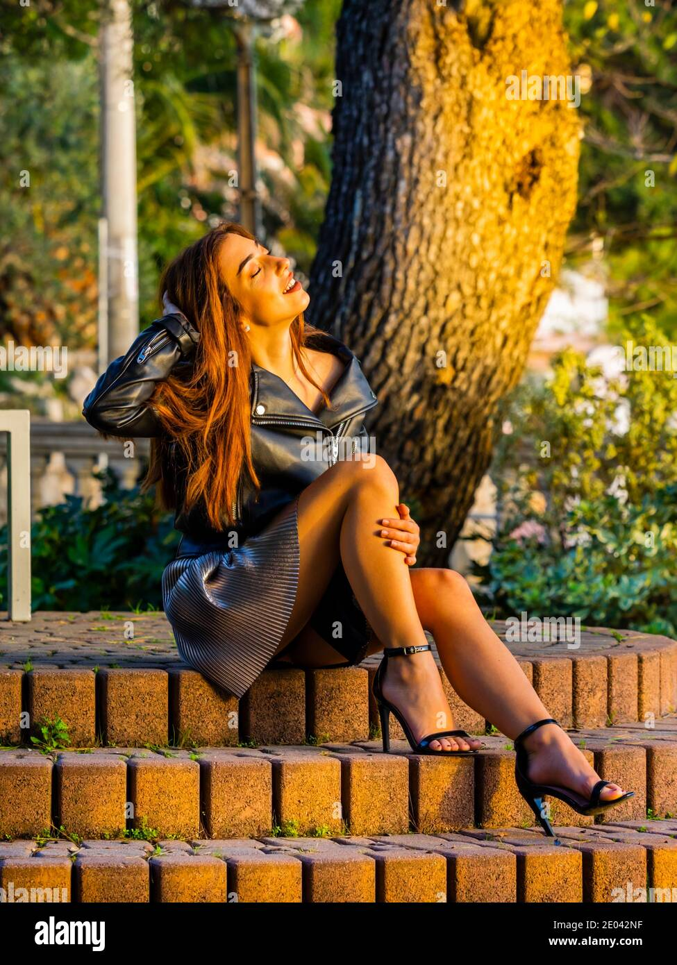 Teengirl sitting seated steps stairs in park daydreaming drunder lit by warm late afternoon sunset light legs heels full length whole body bit sexy Stock Photo