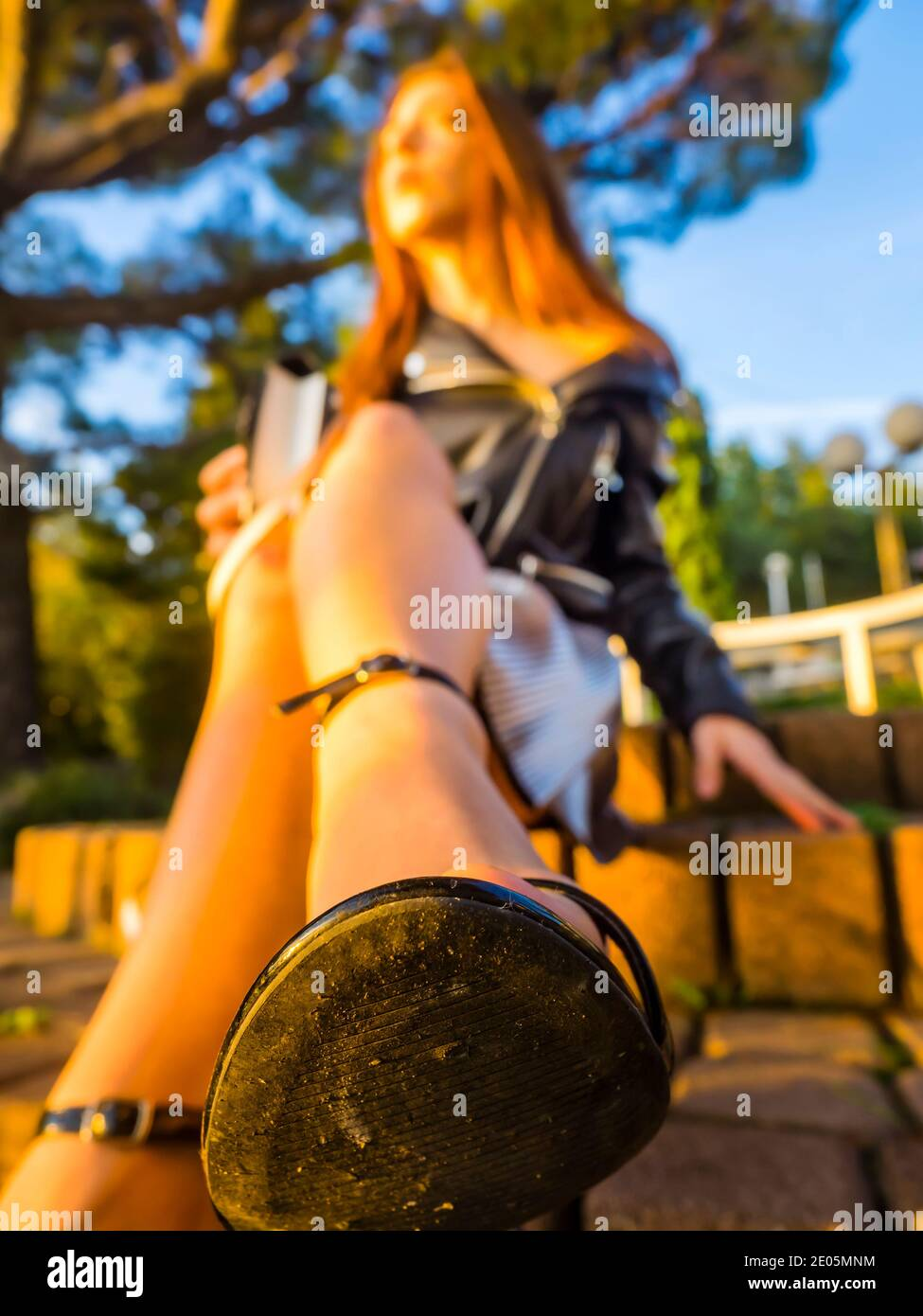 Teengirl sitting in park under lit by warm late afternoon sunset light legs heels full length whole body closeup close-up macro on shoe tip isolated Stock Photo