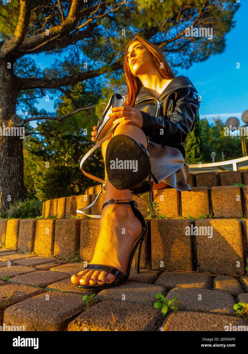 Teengirl sitting in park on steps under lit by warm late afternoon sunset light legs heels full length whole body Stock Photo