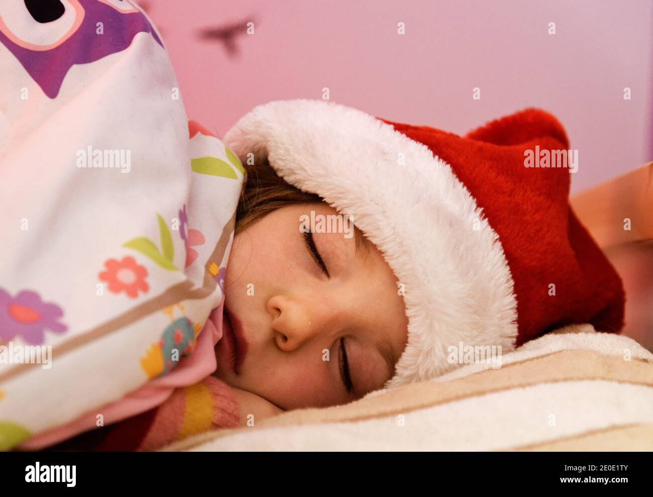 A little girl (6 yr old) asleep in bed with her christmas hat on Stock Photo